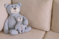 Toy bears sitting on a sofa. Toy bears -father and son- sitting on a sofa, toned Royalty Free Stock Photos