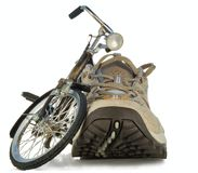 A toy bicycle and running shoes. On a white background Stock Images