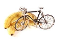Toy bike stand next to bananas. Toy metal bike stand next to bananas Royalty Free Stock Images