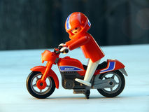 Toy biker on red bike. Red bike and a red and white biker with helmet. Plastic toy Royalty Free Stock Photography