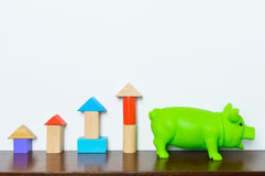 Toy block as Graph rising up to piggy bank saving finance concept Royalty Free Stock Image