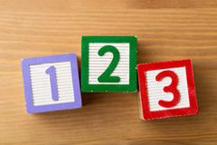 123 Toy block. Over the wooden background Stock Photos