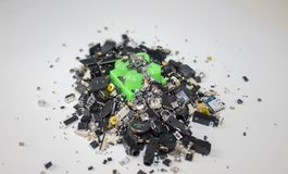 A toy block stuck in SMT components. A pile of surface mounted components over a toy green block royalty free stock photo