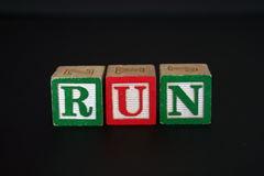 Toy blocks that spell RUN. Toy blocks that spell out RUN, isolated on black background Stock Image