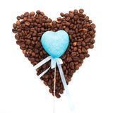 Toy blue heart lie on the circle of roasted coffee beans laid out in the form of heart isolated on white background Royalty Free Stock Images