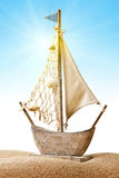 Toy boat on sand. Old fashioned toy sailing boat on sand with blue sky background Stock Images