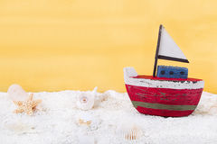 Toy boat and seashells on yellow background Stock Images