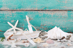Toy boat with starfish and seashells with a wooden turquoise background, postcard royalty free stock photography
