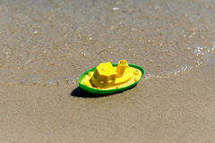 Toy boat in the wet sand of the sea. Summer holidays at sea. Boat trips. Royalty Free Stock Photos