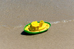 Toy boat in the wet sand of the sea. Summer holidays at sea. Boat trips. Stock Photography