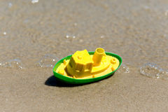 Toy boat in the wet sand of the sea. Summer holidays at sea. Boat trips. Royalty Free Stock Photography