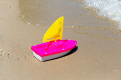 Toy boat in the wet sand of the sea. Summer holidays at sea. Boat trips. Stock Photos