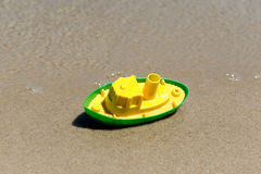 Toy boat in the wet sand of the sea. Summer holidays at sea. Boat trips. Royalty Free Stock Images