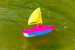 Toy boat in the wet sand of the sea. Summer holidays at sea. Boat trips. Royalty Free Stock Image