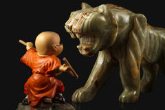 Toy boy figure and stone figure of a tiger Royalty Free Stock Photos