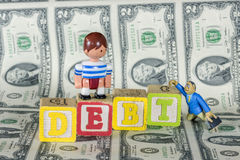 Toy boy and man with word debt on mony Stock Photo