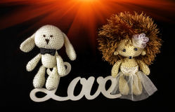 Toy braided newlyweds, the bride and groom at sunset. word love. Stock Photos