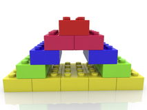 Toy bricks in various colors stacked in pyramid Stock Photo