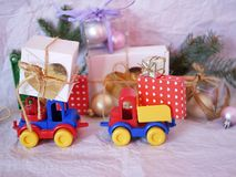 Toy bright cars deliver boxes with gifts, Christmas decorations, New Year`s deco