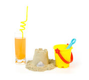 Toy bucket, sandcastle and a refreshing drink Royalty Free Stock Photo