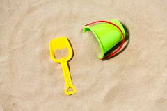 Toy bucket and shovel on beach sand. Toys, childhood and summer concept - bucket and shovel on beach sand stock photo