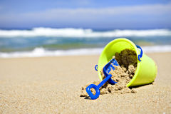 Toy bucket and shovel on an empty beach Stock Photos