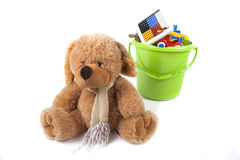 Toy bucket and toy bear. A toy bear is in front of a green toy bucket which is full with different and colored toys Stock Images