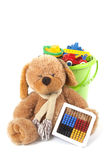 Toy bucket and toy bear. A toy bear is in front of a green toy bucket which is full with different and colored toys Royalty Free Stock Photos