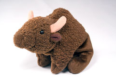 Toy Buffalo. Closeup shot of a cute brown plush (stuffed) toy buffalo sitting on his haunches. Shot in studio light on a white background Royalty Free Stock Images