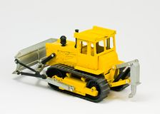 Toy bulldozer. Small model bulldozer isolated on white background - back view Stock Images