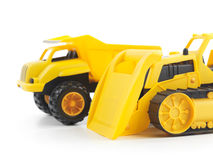 Toy bulldozer and dump truck. Yellow plastic children toys a bulldozer and a dump truck isolated on white background Stock Photo