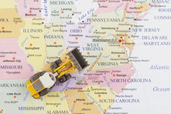 Toy bulldozer over the American map. Bulldozer on map royalty free stock images