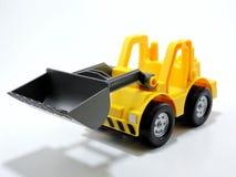 Toy Bulldozer plástico amarillo en el fondo blanco Fotografía de archivo