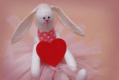 Toy Bunny avec la participation rouge de coeur Carte postale au jour du ` s de Valentine Jour du `s de mère Fond rose Photographie stock libre de droits