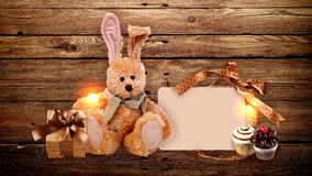 A toy Bunny with gifts and sweets on wooden background. Stock Photos