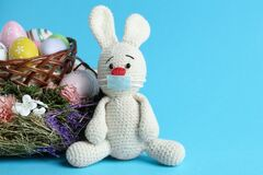 Free Toy Bunny In Protective Mask Near Wicker Basket With Eggs On Light Blue Background. Easter Holiday During COVID-19 Royalty Free Stock Photo - 209520675