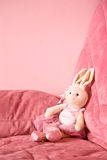 Toy bunny on pink couch Stock Image