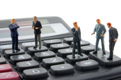 Toy business man on calculator isolated Royalty Free Stock Photography