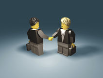 Toy business people handshake. Two toy brick businessmen figures with briefcases making an agreement Stock Images