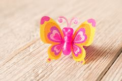 Toy butterfly on a wooden table. Children`s toy royalty free stock image