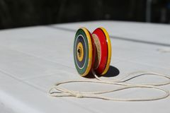 A toy called `Yo-yo` is on a table. A colorful toy tla t is called `Yo-Yo` is on a white table ready to be used Royalty Free Stock Image