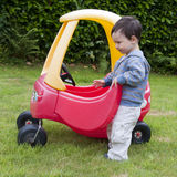 Toy car. A small toddler child playing with a red and yellow toy car on a grass lawn stock image
