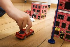 Toy car. A child's hand can be seen, holding on to a toy car and moving it through miniature toy streets and buildings stock image