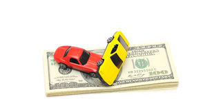 Toy Car Accident Over A Lot Of Dollar Bills Stock Photo