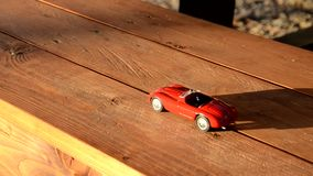 Toy car on a bench. Toy car travels on a bench stock footage