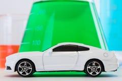 Toy Car bianco davanti al flacone erlenmeyer con liquido verde dentro immagini stock