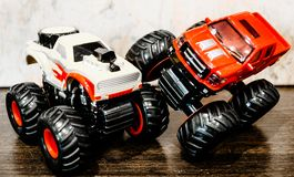 Toy car. Bigfoots. Red and white Bigfoot pickups. Childhood. One Bigfoot hit the other with the front wheel. Toy car. Bigfoot. Red vs white Bigfoot pickup royalty free stock photo