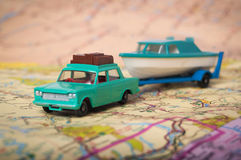 Toy car and boat vacation. Toy car and boat on a road map shot with a shallow depth of field Royalty Free Stock Photos