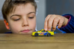 Toy car. Boy playing with toy car on a table, shallow depth of field stock photography