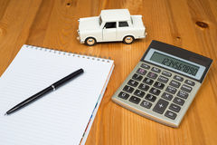 Toy car and calculator. Concept for buying, renting, fuel or service and repair costs Stock Photo